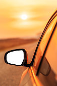 Mock up side view mirror of car on road in autumn sunset