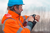 Forestry technician checking up on his smart watch