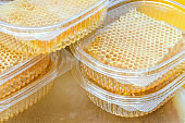 Plastic containers with fresh honey in wax cells on the market. Selective focus.