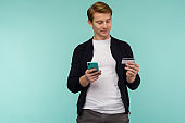 Cheerful sports red-haired guy conducts online payment and looks at the smartphone screen on a blue background.