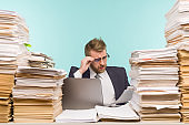 Business executive holds a video conference in the office and piles of paperwork, he is overloaded with work