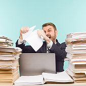 Business executive working in the office and piles of paperwork, he is overloaded with work