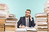 Business executive talking on the phone working in the office and piles of paperwork, he is overloaded with work