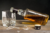 Broken glass and a bottle of whiskey. The concept of ruined life due to alcoholism.
