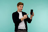 Cheerful sporty red-haired guy shows a finger on the smartphone screen on a blue background.