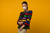 Beautiful slim girl fashion model posing in a protective respirator on a yellow background.