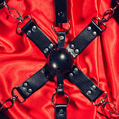 Top view of bdsm outfit. Bondage and close up Gag ball on the red linen. Adult sex games. Kinky lifestyle.
