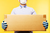 Man holding cardboard boxes in medical rubber gloves and mask.