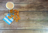A tall glass of light beer, a handful of pritzel and a traditional Bavarian napkin on a wooden table.