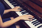 Beautiful female hands on the keys of an old piano