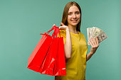 Photo of cheerful young woman holding fan of money and red shopping bags, isolated on blue background