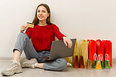 Young woman doing online shopping at home using laptop.