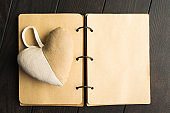 Ol open craft notebook with hadmade fluffy heart over brown wooden background with copy space. Flat lay