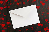 Valentine's day's letter in white closed envelope over brown wooden background with red hearts