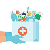 Hands in disposable gloves with paper bag with medicines, drugs, pills and bottles inside