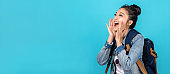 Banner of happy asian woman travel backpacker shouting open mouth to copyspace on blue background. Cute asia girl smiling wearing casual jeans shirt and looking to aside for present promotions.