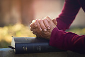 Hands folded in prayer on a Holy Bible   Religion Concept
