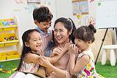 Kindergarten teachers and children embrace together