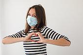 Female in mask gesturing heart