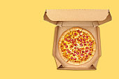 Pepperoni pizza in brown take-out box on yellow background.