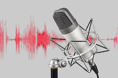 Silver colored condenser microphone on waveform background