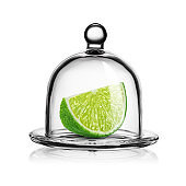 Slice of green lime in glass bell jar isolated on white.