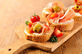 tapas- bread slice with cheese, prosciutto and olive