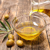 olive oil pouring in bowl with green olive and herb