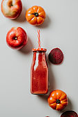 Red smoothie drink in bottle with straw surrounded by red apples, tomatoes and beets