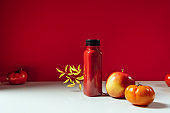 Red smoothie drink in bottle surrounded by red apples and tomatoes