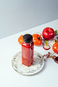 Red smoothie drink in bottle surrounded by red apples, tomatoes and beets, front view