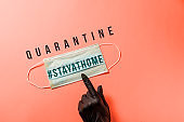 "Covid-19. Hand in black protective glove, points out surgical mask with the message ""STAY AT HOME-QUATANTINE""., Virus prevention and quarantine concept"