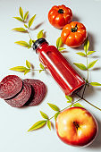 Red smoothie drink in bottle surrounded by red apples, tomatoes and beets