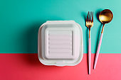 Healthy food concept: white burguer packaging closed with golden fork and spoon
