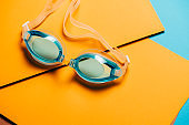 Blue swimming glasses, with rubber strap on yellow geometric background.