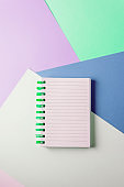 notebook with blank sheet and green spiral on a colorful pastel background