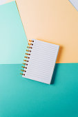 notebook with blank sheet and golden spiral on a colorful pastel background