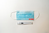 "quarantine. Surgical mask and digital thermometer with text ""covid-19,""Coronavirus pandemic on white background"