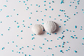 White sea shell surrounded by blue sand on bright background, Summer time concept