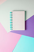 notebook with blank sheet and blue spiral on a colorful pastel background