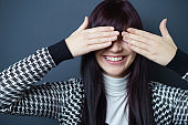 Playful Young Woman Covering Eyes with Hands