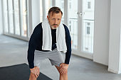 Man crouching forward with bent knees in a gym