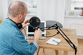 Man adjusting pop filter on microphone at home