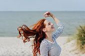 Carefree young woman tossing her long red hair