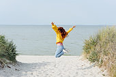 Girl in yellow jumping for joy on the beach