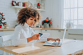 Serious lady inserting bank information for online shopping