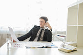 Successful young businessman sitting at his office desk talking on the phone