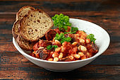 Bean and chorizo stew served in white bowl with parsley