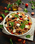 Pasta salad with tomato, black olives, cucumber and feta cheese in white plate. healthy food.