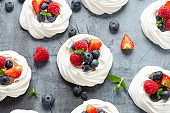 Meringue nest mini pavlova cake with fresh berries strawberry blueberry raspberry and mint for healthy desert.